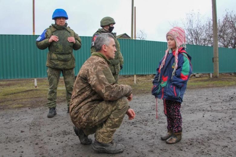Анатолий присел на колено и попросил у ребенка прощения за действия своих сослуживцев. Искренне ли? Фото: Андрей ТРУБЕЦКИЙ